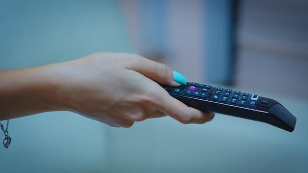 Fernsehfernbedienung in den händen einer frau, die auf den fernseher zeigt und die kanäle wechselt. nahaufnahme einer frau, die den controller hält und den knopf drückt, der auf der couch vor dem fernseher sitzt.