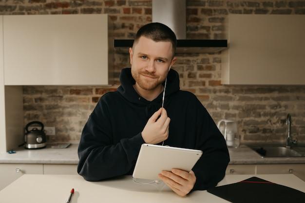 Fernstudium online. ein mann mit bart, der aus der ferne auf seinem tablet studiert. ein glücklicher kerl, der online unterricht sieht.