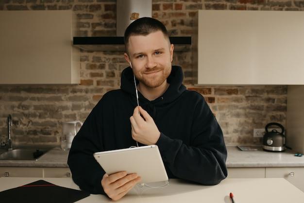 Fernstudium online. ein mann mit bart, der aus der ferne auf seinem tablet studiert. ein glücklicher kerl mit einem lächeln, der online unterricht sieht.