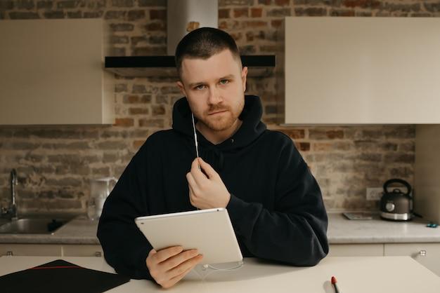 Fernstudium online. ein mann mit bart, der aus der ferne auf seinem tablet studiert. ein kerl, der online unterricht sieht.