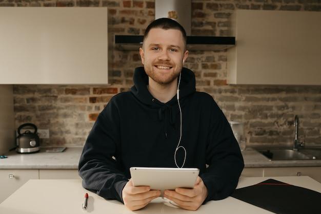 Fernstudium online. ein mann mit bart posiert mit seiner tafel. ein kerl, der online in seiner eigenen küche unterricht sieht.