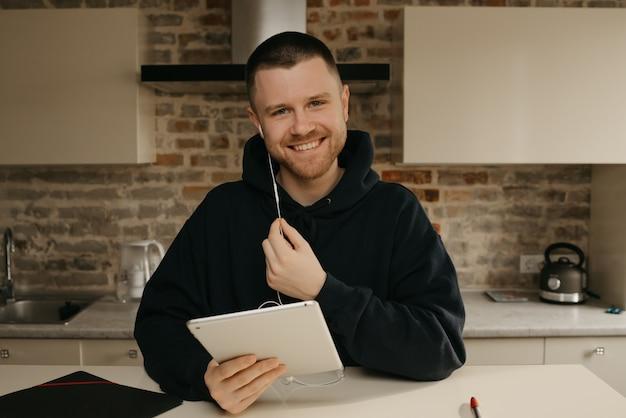 Fernstudium online. ein mann mit bart posiert mit seiner tafel. ein kerl, der online unterricht sieht.