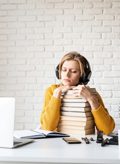 Fernunterricht. e-learning. junge frau im schwarzen kopfhörer, der hörbuch mit geschlossenen augen hört, die mit einem stapel bücher sitzen