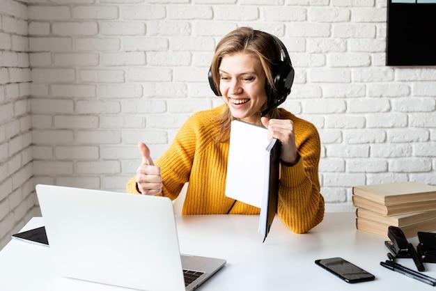 Fernunterricht. e-learning. junge frau in den schwarzen kopfhörern, die online unter verwendung des laptops studieren, der daumen hoch zeigt