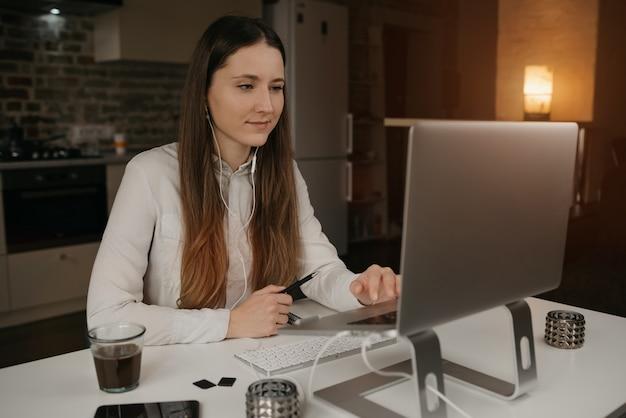 Fernunterricht. eine kaukasische frau mit kopfhörern, die entfernt online auf ihrem laptop studiert. ein mädchen, das ein webinar an ihrem gemütlichen heimarbeitsplatz beobachtet.