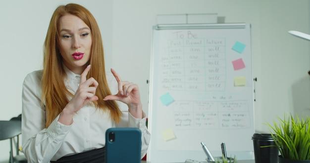 Fernunterricht für schulkinder, ein junger moderner lehrer führt online-unterricht für schüler mit einem smartphone während der quarantäne durch und unterrichtet kinder.