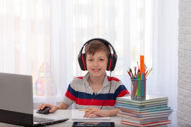 Fernunterricht kind, das hausaufgaben mit digitalem tablett schreibt. konzept online-bildung.