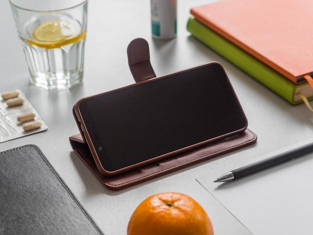 Fernunterricht oder arbeit, online-bildungskonzept. arbeitsplatz. smartphone, bücher, glas wasser mit zitrone und pillen auf dem tisch.