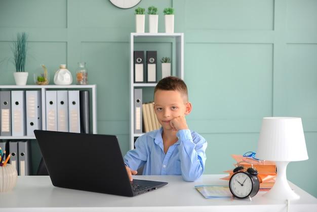 Fernunterricht online-bildung ein schuljunge lernt zu hause und macht schulhausaufgaben
