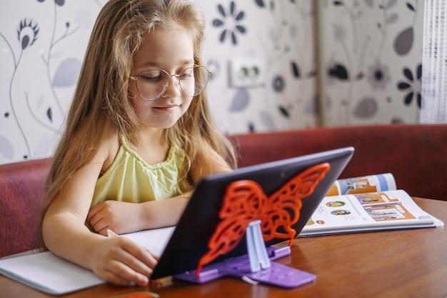Fernunterricht. online-lernen zu hause. kleines mädchen unterrichtet englisch, spricht online mit einem lehrer.