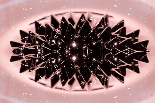 Ferromagnetisches flüssiges phänomen mit rosa hintergrund