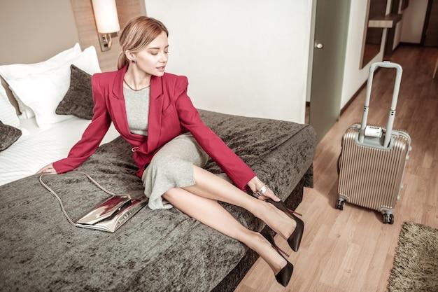Fersen ausziehen. blonde frau, die schwarze schuhe mit hohen absätzen auszieht, nachdem sie in ihr hotel gekommen ist