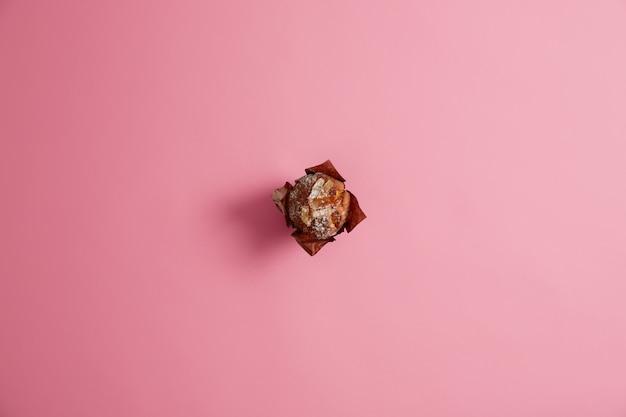 Fertig gebackener muffin gepudert mit zucker in braunem papier lokalisiert auf rosa hintergrund. frische süßwaren, süßes leben, junk-food-konzept. frühstück. dessert für feinschmecker. selektiver fokus.