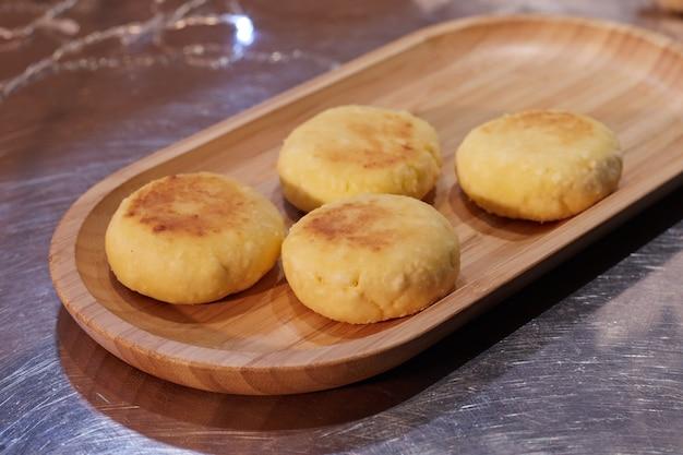 Fertig gebratene käsekuchen liegen in einem teller auf einem tablett auf dem tisch, der hintergrund ist verschwommen