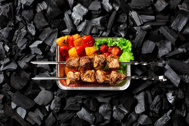 Fertig schaschlik. gegrilltes gemüse und fleisch am spieß in einem einwegbehälter aus aluminium.