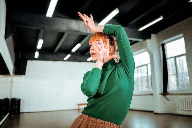 Fertig werden. der rothaarige professionelle choreograf mit dem haarknoten sieht dramatisch aus, während er sich auf die aufführung vorbereitet