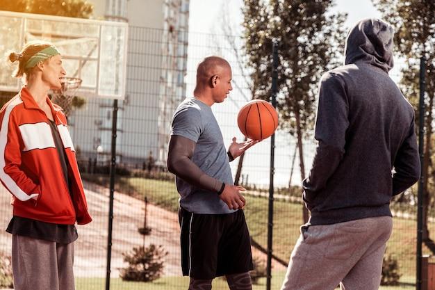 Fertig zu spielen. positive nette männer, die zusammen auf dem basketballplatz stehen, während sie sich auf das spiel vorbereiten