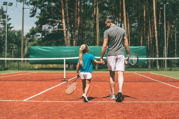 Fertig zu spielen. vollständige rückansicht eines kleinen blonden mädchens in sportkleidung, das tennisschläger trägt und ihren vater ansieht, der in ihrer nähe durch den tennisplatz geht?