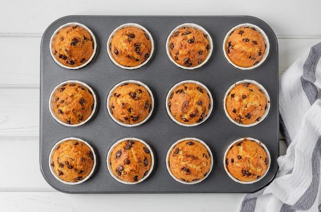 Fertige muffins mit schokoladenstückchen in backform auf weißem holzhintergrund. rezept schritt für schritt. ansicht von oben.