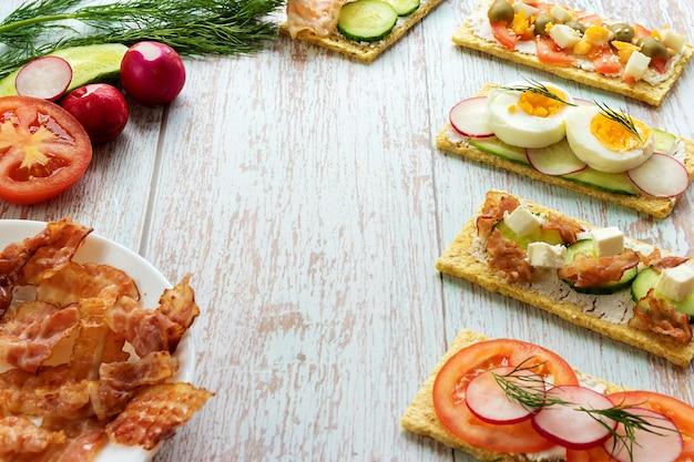 Fertige snacks mit korrektem essen mit zutaten auf einem hellen holzhintergrund mit platz für text