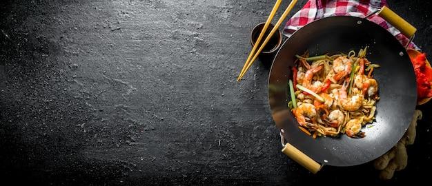 Fertige udon-nudeln in einer wok-pfanne mit sojasauce, essstäbchen und einer serviette auf schwarzem holztisch