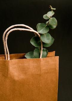 Fertigen sie braunen papiereinkaufstaschenschwarzhintergrund an frühlingskonzept