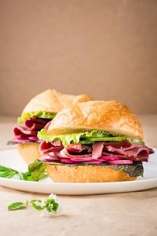 Fertiger hamburger mit pastrami, gemüse und basilikum auf einem teller auf kraftpapier. amerikanisches fastfood.. platz kopieren
