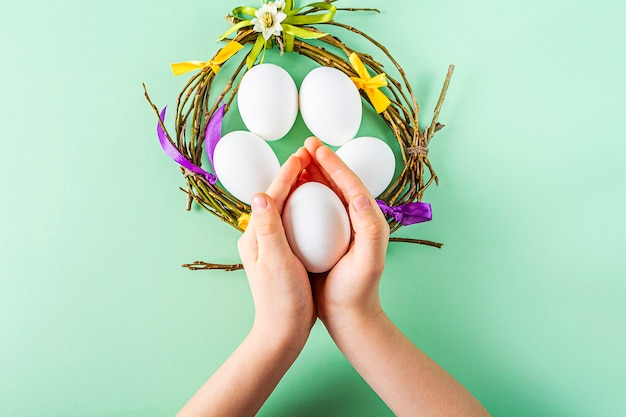 Fertiges nest oder kranz mit bunten bändern kinderhänden, die ei halten