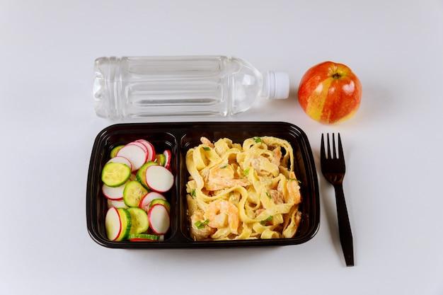 Fertiggericht auf lebensmittelbehälter mit wasser und apfel zu essen.