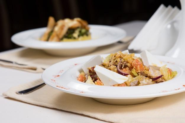 Fertiggerichte in weißen schalen an einfachen gedecken serviert auf einem restauranttisch für zwei