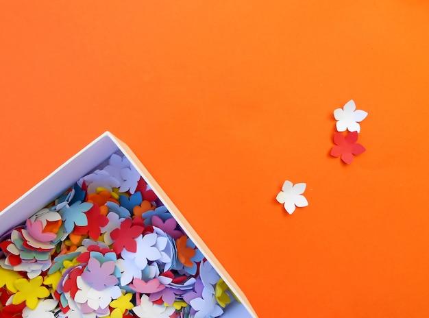 Fertigkeitkasten mit papierblumen auf orange hintergrund
