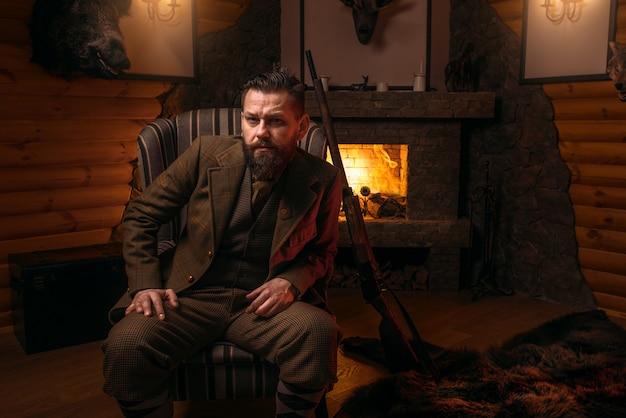 Feste männliche jäger in traditioneller jagdkleidung, die in einem stuhl gegen brennenden kamin sitzt.