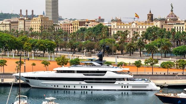 Festgemachte yacht im mittelmeerhafen, gebäude, straße, grün in barcelona, spanien