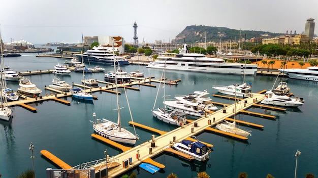 Festgemachte yachten im mittelmeerhafen, gebäude, grün in barcelona, spanien
