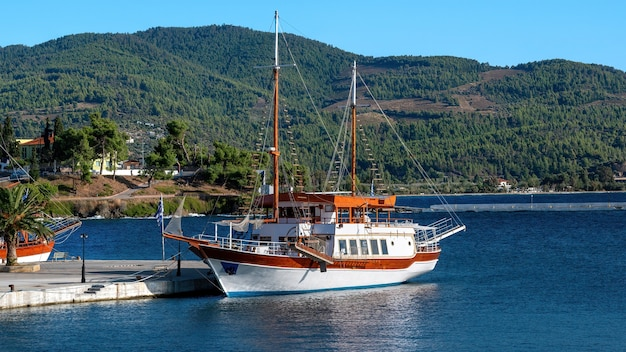 Festgemachtes segelboot nahe einem pier in neos marmaras, grüner hügel, griechenland