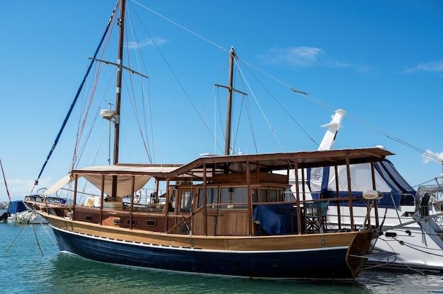 Festgemachtes vintage segelboot im ägäischen seehafen, aus holz, yachten um ihn herum in nikiti, griechenland