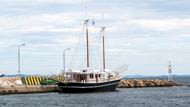 Festgemachtes vintage segelboot nahe einem pier mit einem mann an bord im seehafen, ägäisches meer in ormos panagias, griechenland