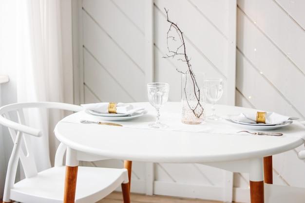 Festlich gedeckter tisch für zwei, minimalistische weihnachtsdekoration. skandinavisches interieur
