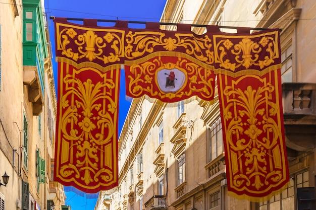 Festlich geschmückte straße mit bannern für st. augustine feast in der altstadt von valletta, malta. flammendes, von pfeilen durchbohrtes herz - symbol des heiligen augustinus