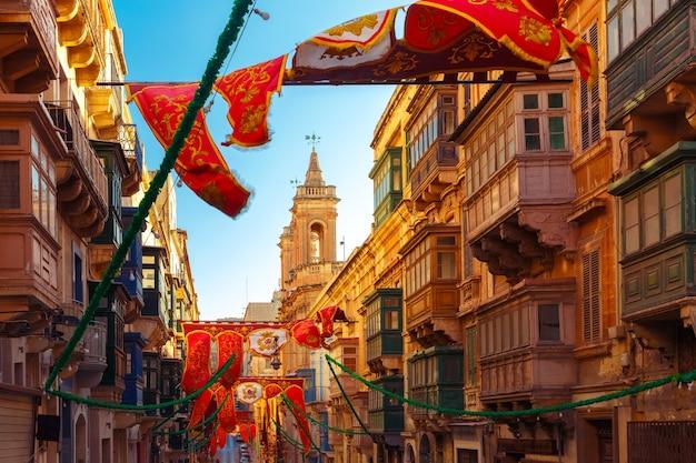 Festlich geschmückte straße mit bannern für st. augustine feast in der altstadt von valletta, malta