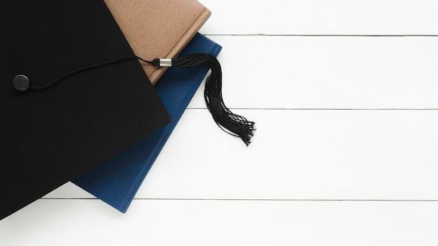 Festliche abschlusskomposition mit akademischer kappe und büchern