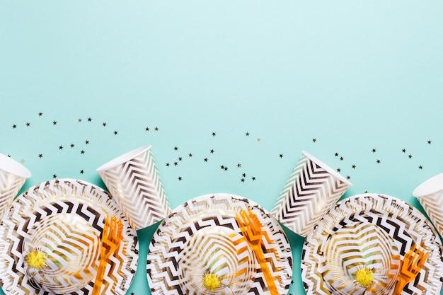Festliche accessoires für party in goldtönen auf türkisfarbenem hintergrund.