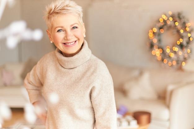 Festliche atmosphäre, dezember- und weihnachtsferienkonzept. selbstbewusste glückliche reife kurzhaarige frau im stilvollen pullover, der neujahrsvorbereitungen macht, wohnzimmer verziert, freudig lächelt
