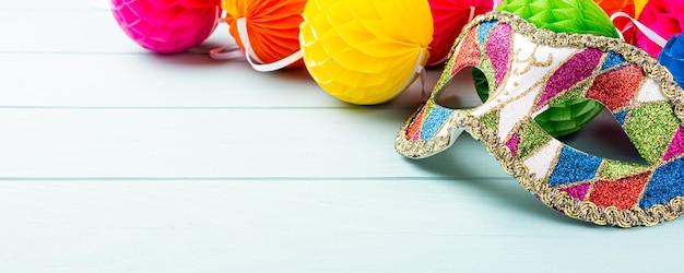Festliche blaue oberfläche mit bunter karnevalsmaske. grußkartenkonzept für geburtstag, karneval, party. kopieren sie platz, banner