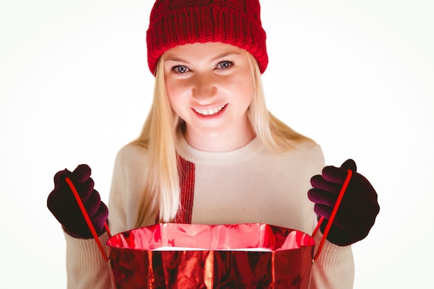 Festliche blondine, die eine geschenktasche öffnet