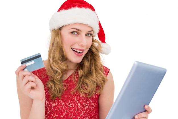 Festliche blondine, die ihren kreditkarte- und tabletten-pc verwenden