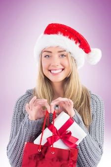 Festliche blondine, die weihnachtsgeschenk und -tasche hält