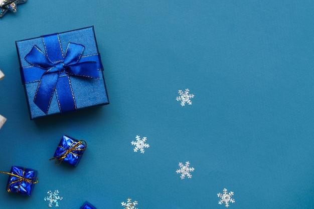 Festliche box nahaufnahme blaue schleife auf blauem hintergrund mit weihnachtskugeln und schneeflocken neujahr christus...