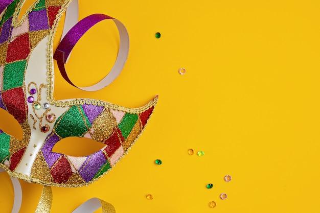 Festliche, bunte karneval- oder karnevalsmaske und accessoires über gelber wand. flache lage, draufsicht, kopierraum