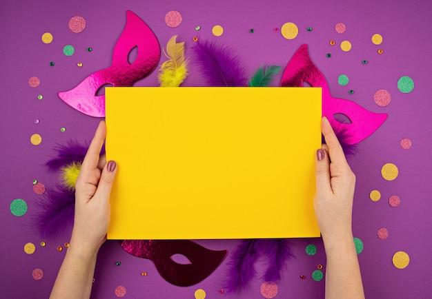Festliche, bunte karneval- oder karnevalsmaske und accessoires über lila wand. flache lage, draufsicht, kopierraum
